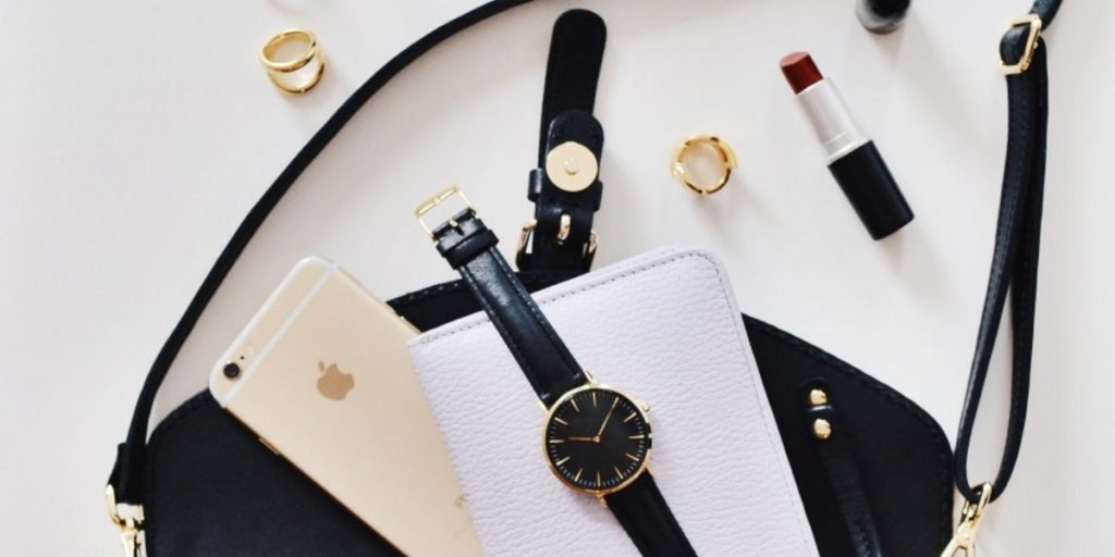 A flat-lay of handbag contents, including red lipstick, a black leather strapped watch and a golden iPhone