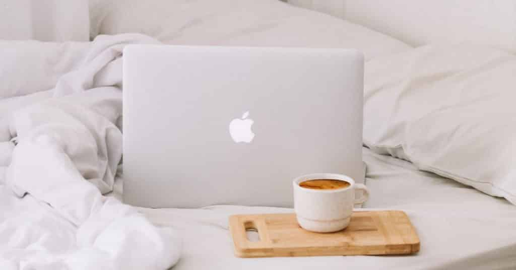 Ethical Brand Directory Blog | Top 10 Tips for Going Green | Cup of coffee and laptop on a bed
