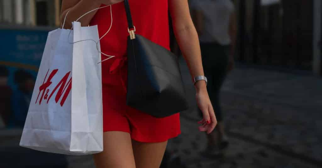 Ethical Brand Directory Blog | Conscious Shopping: How Small Changes Can Make a Big Difference | Woman with fast fashion shopping bag