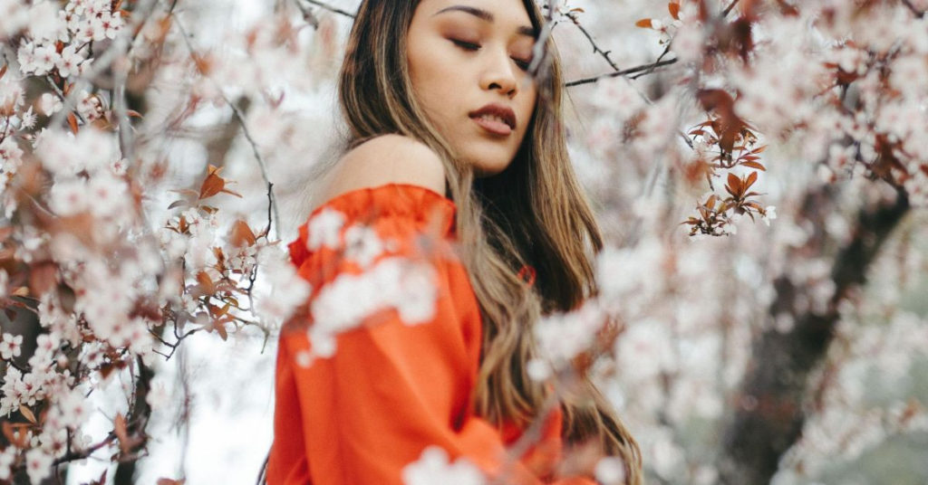 Ethical Brand Directory Blog | Stylists Picks: Spring Wardrobe Essentials | Model wearing red dress posing next to cherry blossom tree